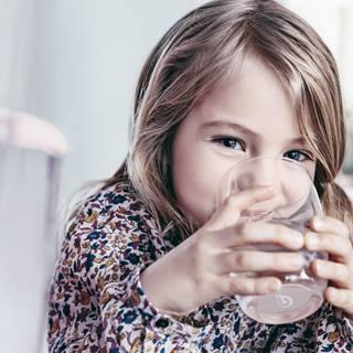 Fille qui boit de l'eau dans un verre